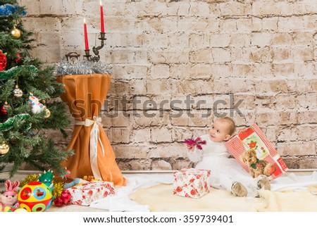 A small child - a girl unpacks near a Christmas tree Christmas gifts - stock photo