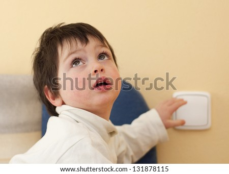 A small child, boy or girl, looking up and reaching to a light switch. - stock photo