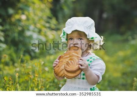 A small child eating a bun. - stock photo
