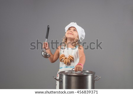 A small child holding a ladle, thoughtfully looking up, smiling and preparing food in a large pan. - stock photo
