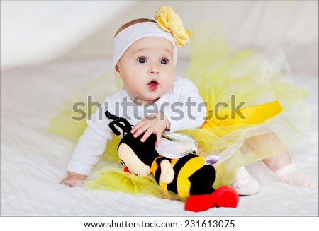 A small child in a yellow skirt sits on the bed with a toy bee - stock photo
