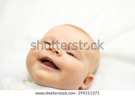 a small child is lying and smiling on white - stock photo