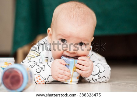 A small child, newborn, lying on the floor and playing with jars and eats puree their food.