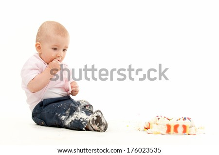 A small child sitting by a birthday cake. - stock photo