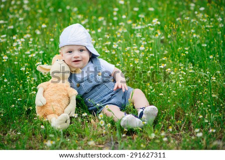 A small child sitting on the lawn with daisies - stock photo
