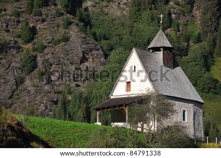 A small church between mountains during summer