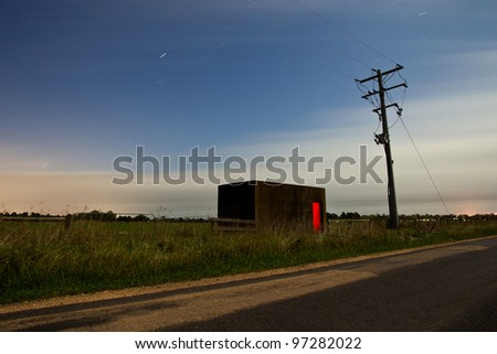 A small concrete building next to a telephone pole. Taken at night under full moon. - stock photo