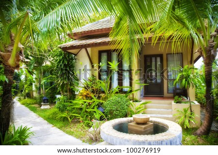 A small cottage among tropical palm trees - stock photo