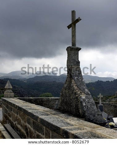 A small countryside stone cemetery in a stormy day.