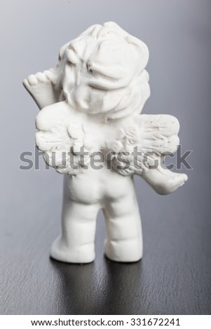 a small cute ceramic angel statuette over a dark surface