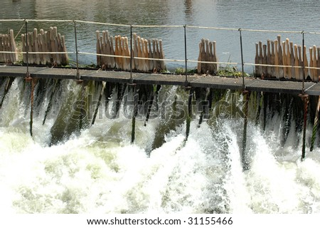 A small dam on a small river. - stock photo