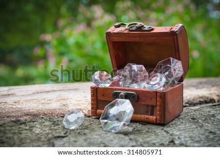 A small decorative treasure chest with diamonds in nature - stock photo