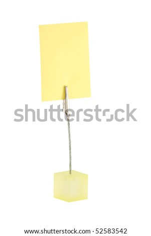 A small desktop note/memo holder, holding a yellow postit (blank so that any text can be placed on it). - stock photo
