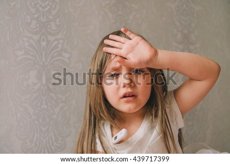 A small diseased girl in the bedroom. Little girl sitting on a bed wearing a pajamas. girl is sick. girl measures the temperature. She feels bad. Sick little girl lying in the bed with thermometer - stock photo