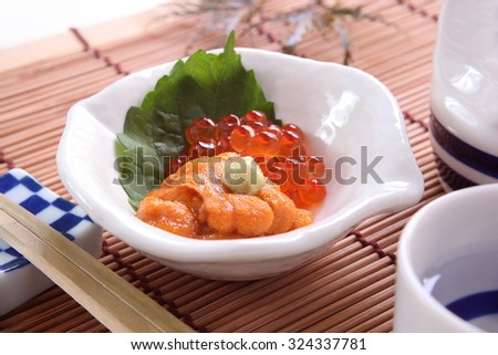 a small dish of Salmon roe, and sea urchin served as an appetizer before the main meal in a Japanese meal/ Sea urchin, and salmon roe - stock photo