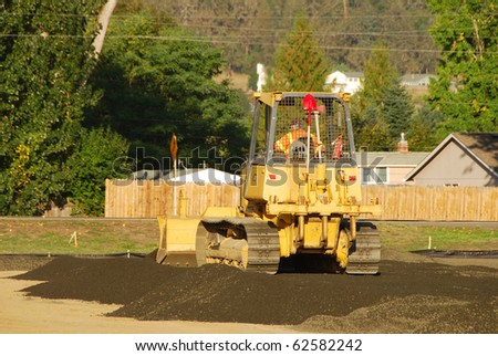 A small dozer laying down base rock while working on new tennis center, Stewart Park, Roseburg OR - stock photo