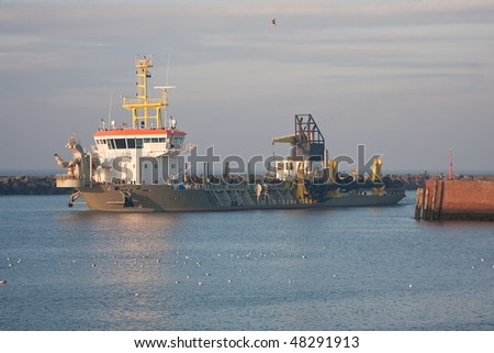 A small dredger entering a harbor - stock photo