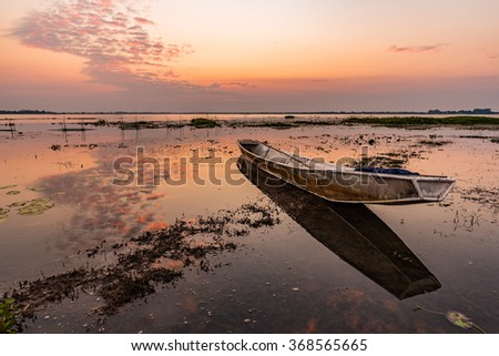 A Small Fishing Boats Was Laid Riverbank At Sunset