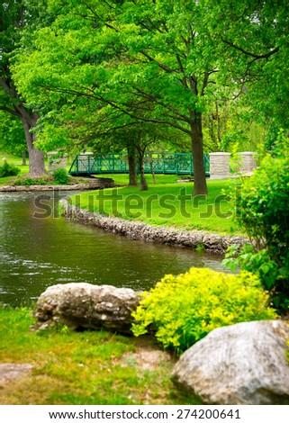 A small footbridge crosses a stream amidst the lush, green foliage of a beautiful park. - stock photo