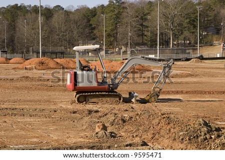 A small front end loader working in a field of dirt - stock photo