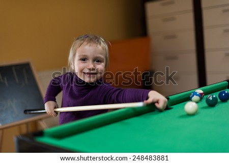 A small girl playing in billiards - stock photo