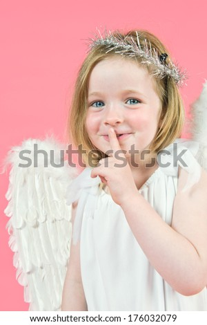 A small girl with angel wing with her finger by her mouth. - stock photo