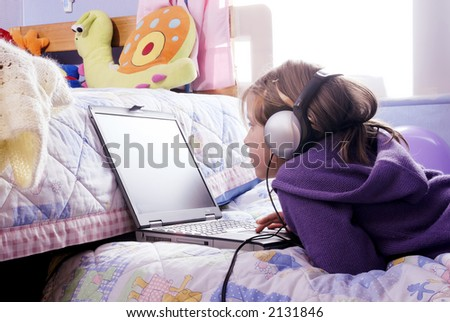 a small girl with headphones using a notebook over her bed - stock photo