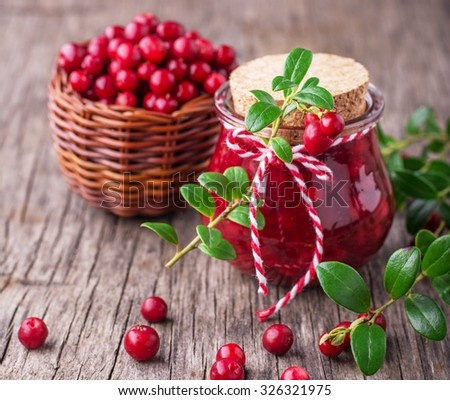 A small glass jar with fresh homemade cranberry sauce on a wooden background with ripe cranberries. selective Focus - stock photo