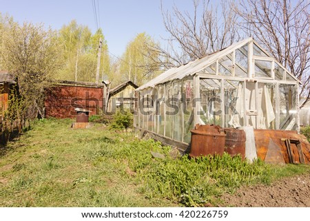 A small greenhouse with air vents in the garden - stock photo