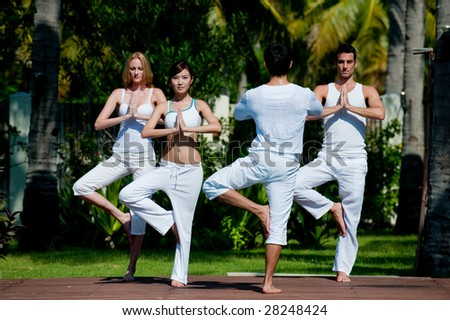 A small group of adults attending a yoga class outside in a tropical setting - stock photo