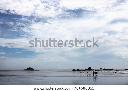 A small group of people walk along a stretch of open Oregon beach