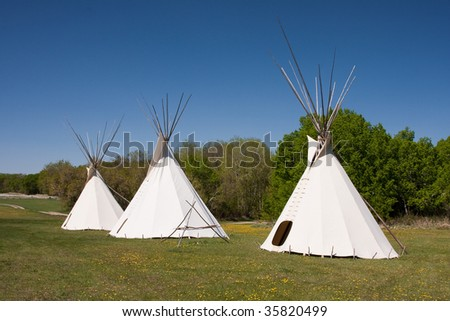 A small group of tepees in a meadow surrounded by forest. Tepees were traditional housing for Native Americans in Great Plains and other Western states. - stock photo