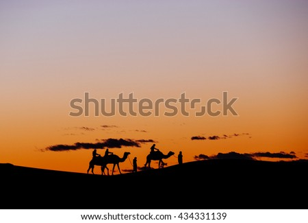 A small group of tourists during a camel trekking at sunset through the Erg Chebbi Dunes. Merzouga, Morocco, Africa. - stock photo