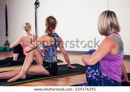 A small group of women are stretching their backs in the gym - stock photo