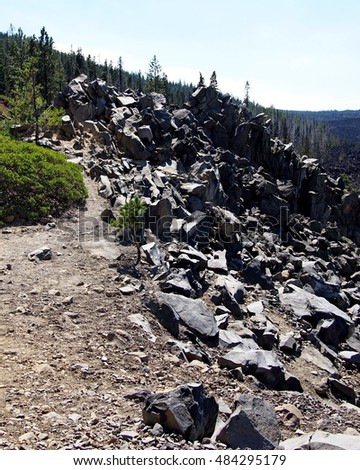 A small hiking path leads to the top of a point full of jagged rocks in the Cascade Mountains of Oregon.
