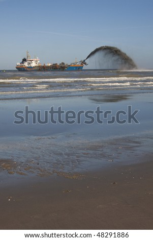 A Small hopper dredger rain-bowing close to the beach - stock photo