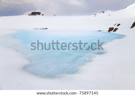 A small icy mountain lake after a frozen winter night during spring - stock photo