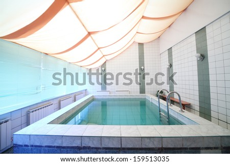 A small indoor pool with tiles on walls and floor and blinds on the windows - stock photo