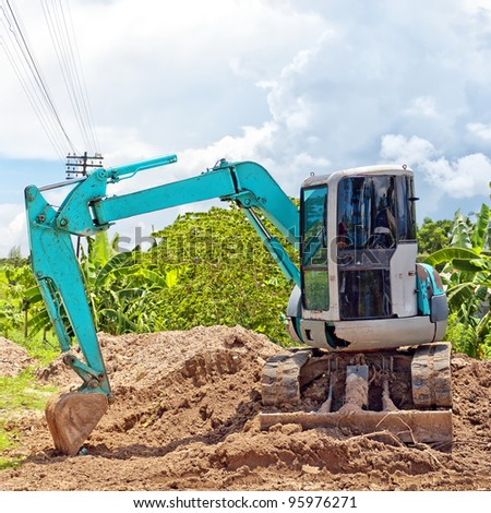 A small industrial digger moves earth at a building site. - stock photo