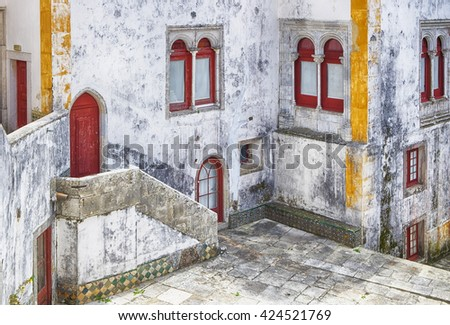 A small interior courtyard in a historic building in Sintra, Portugal shows elements of Moorish influence. The building shows some signs of disrepair with cracked walls and faded paint.