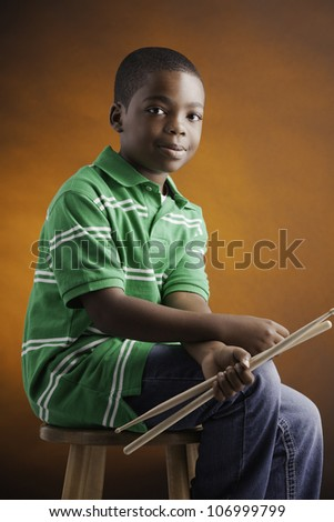 A small isolated African American male child  in a green shirt sitting on a wood stool holding drumsticks and smiling against an orange background. - stock photo