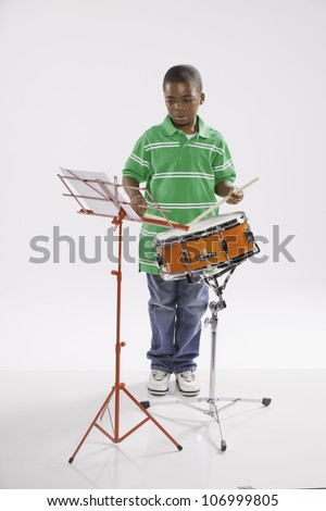 A small isolated African American male child in a green shirt studying how to play a snare drum against a white background. - stock photo