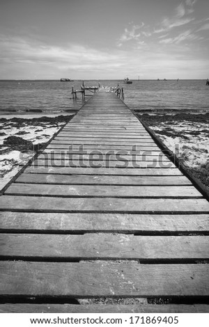 A small jetty sticks out onto the water. In black and white. - stock photo