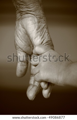 A small kid holding hands of an old woman - stock photo