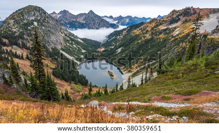 A small lake amidst the scenic autumn mountains shrouded in mist, HEATHER-MAPLE PASS LOOP TRAIL, Washington state - stock photo