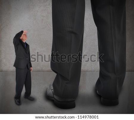 A small little business man is looking up at a large big boss on a textured background. Use it for a power or challenge concept. - stock photo