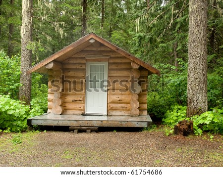 A small log cabin in a forest of trees - stock photo
