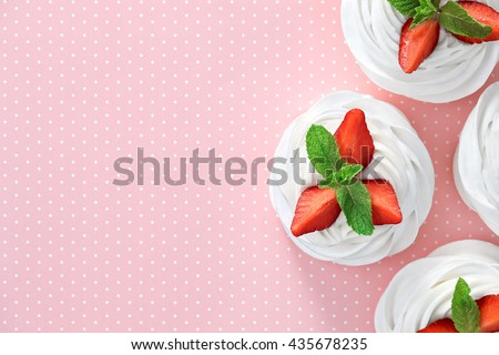 A small meringue Pavlova dessert with some strawberry slices garnished with mint leaves on a pink dotted background. Top view. - stock photo