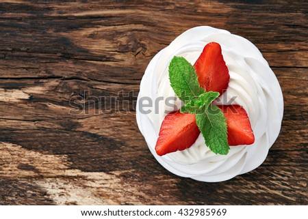 A small meringue Pavlova dessert with strawberry slices garnished with mint leaves on a vintage wooden background. Top view. - stock photo