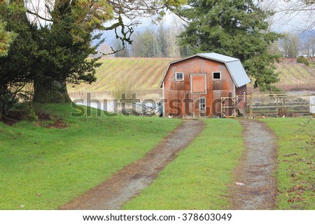 A small, modest barn is found at the end of a dirt road/Small Barn/A small, modest barn is found at the end of a dirt road. - stock photo